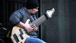 Смотреть Уличный музыкант с огромной гитарой