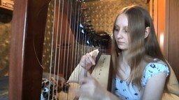 Смотреть Девушка играет на арфе